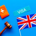 Visa to Britain concept. Text visa near passport cover and british flag, hammer on blue background top view